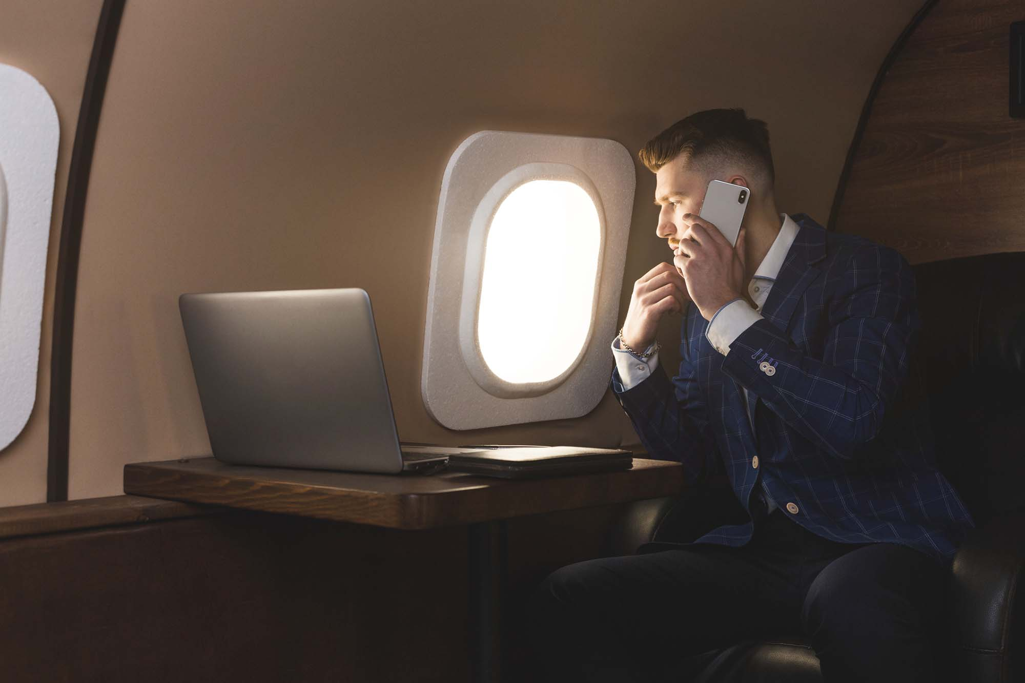 Businessman in an expensive suit working sitting in the chair of his private jet